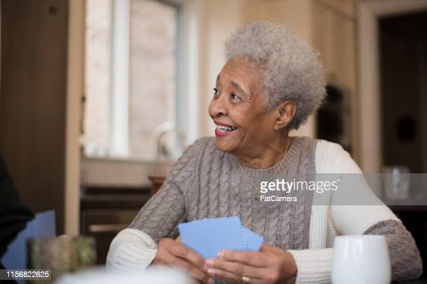 senior woman of african descent playing cards - black suit stock pictures, royalty-free photos & images