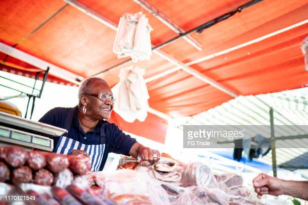 senior woman offering product to a customer of her street market - market vendor stock pictures, royalty-free photos & images