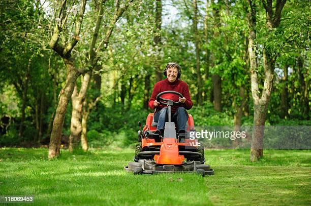 年配の女性は、芝刈り機 - のりものに乗る ストックフォトと画像