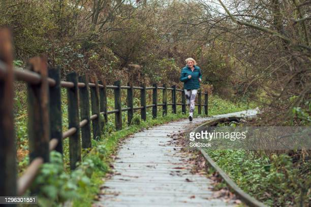 senior woman on a morning run - one senior woman only stock pictures, royalty-free photos & images