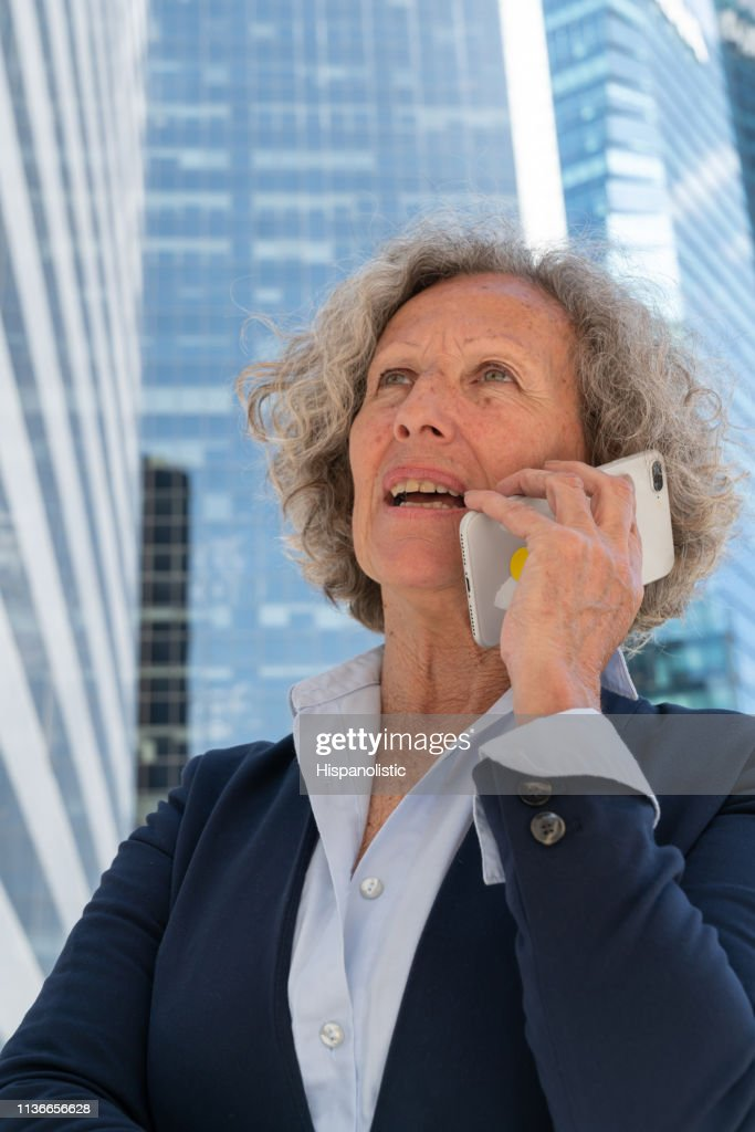 Senior woman on a phone call at a business district looking serious : Stock Photo