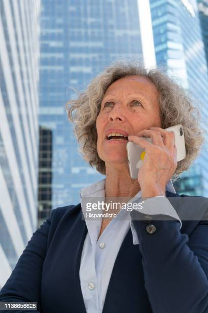 Senior woman on a phone call at a business district looking serious