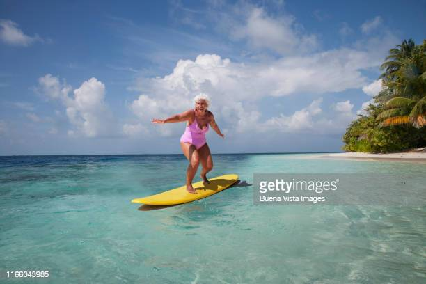 senior woman on a surf board - vilamendhoo stock photos and pictures