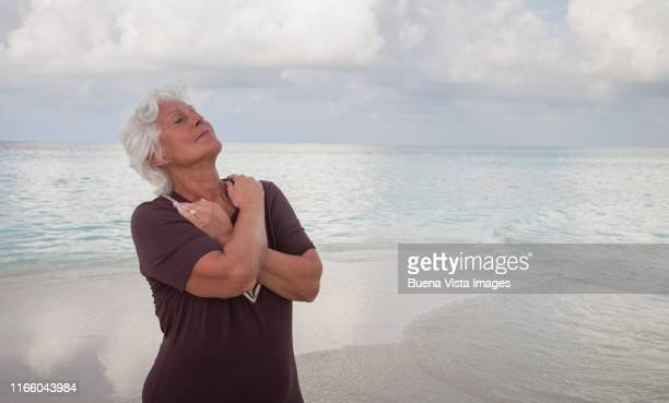 senior woman on a tropical beach - vilamendhoo stock photos and pictures