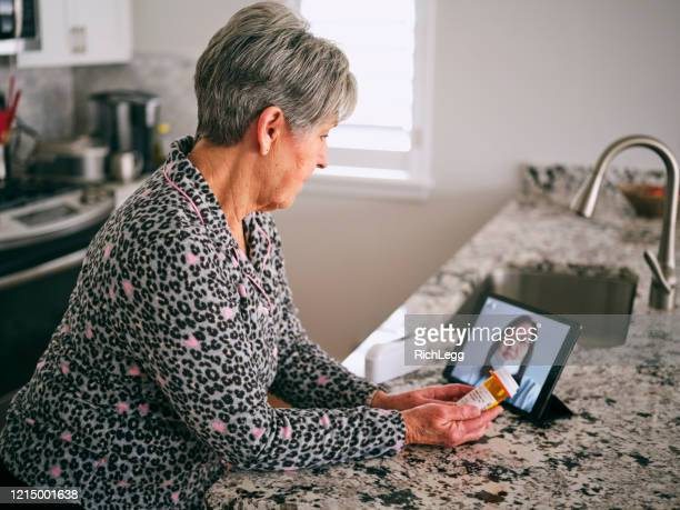 senior woman on a virtual doctor visit - visita imagens e fotografias de stock