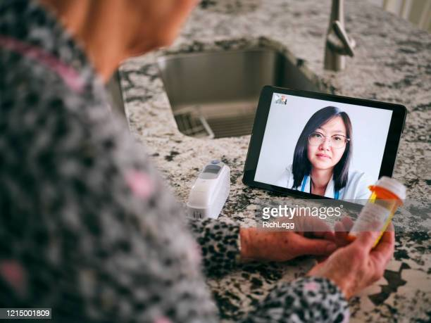 senior woman on a virtual doctor visit - visit stock pictures, royalty-free photos & images