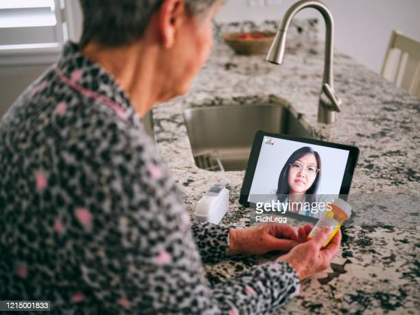 senior woman on a virtual doctor visit - flatten the curve stock pictures, royalty-free photos & images