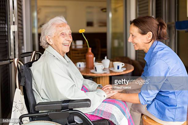 Senior woman on a wheelchair with home caregiver