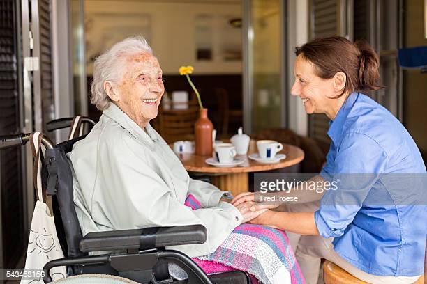 Senior Frau auf einen Rollstuhl mit Altenpfleger