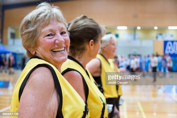 senior woman on basketball court smiling to carmera