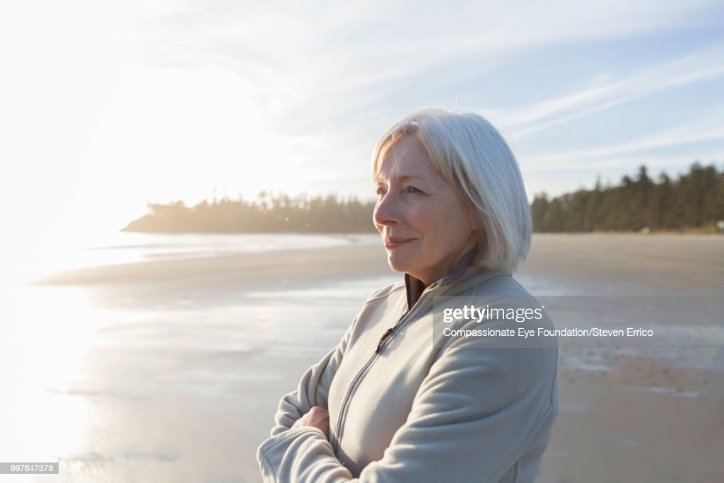 Senior woman on beach looking at ocean view at sunset : Stock Photo