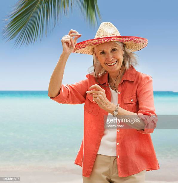 Senior woman on beach  snapping fingers