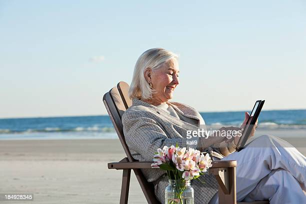 Senior woman on beach using digital tablet.
