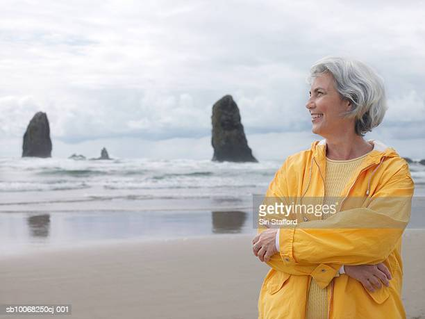 Senior woman on beach with arms crossed, smiling