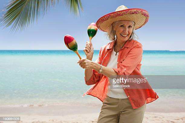 senior woman on beach with maracas - mexican hat stock pictures, royalty-free photos & images
