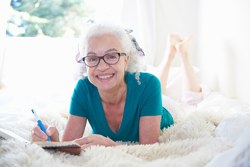 senior woman on bed with diary - gettyimageskorea