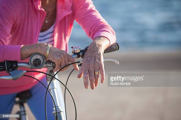 senior woman on bicycle by beach - old women in pantyhose stock pictures, royalty-free photos & images
