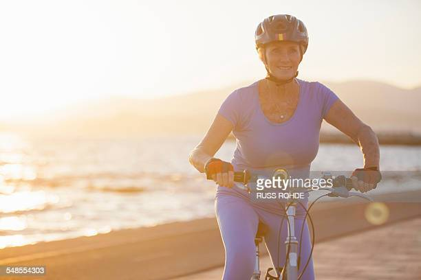 senior woman on bicycle by beach - old women in pantyhose stock photos and pictures