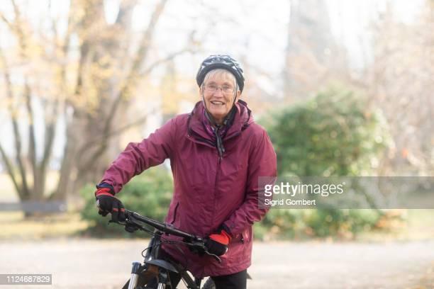 senior woman on bicycle in park - sigrid gombert stock-fotos und bilder