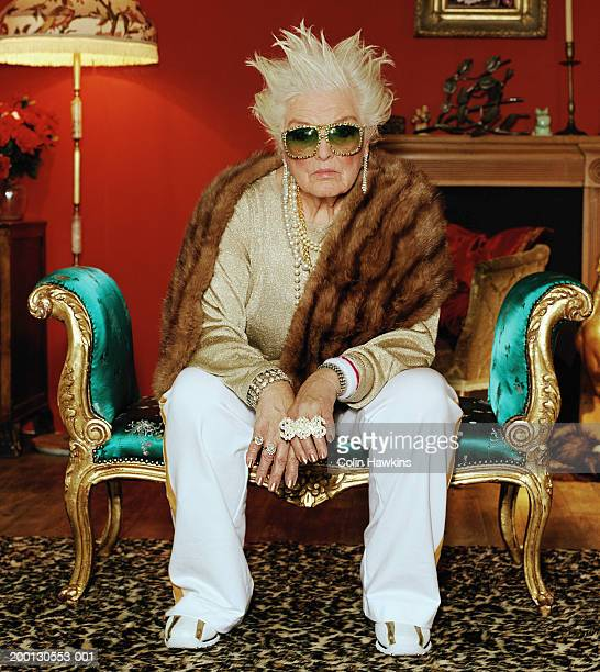 Senior woman on chaise longue, wearing hip hop accessories, portrait