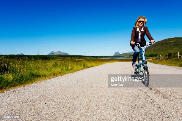 senior woman on folding bike in scotland - foldable stock pictures, royalty-free photos & images