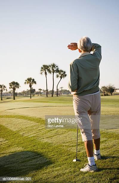 Senior woman on golf course, rear view