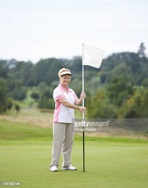 Senior woman on golf green holding flag.