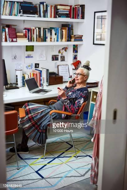 senior woman on phone in home office - disruptaging stock-fotos und bilder