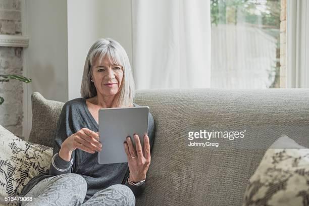 Mulher idosa no sofá em casa com Tablet digital