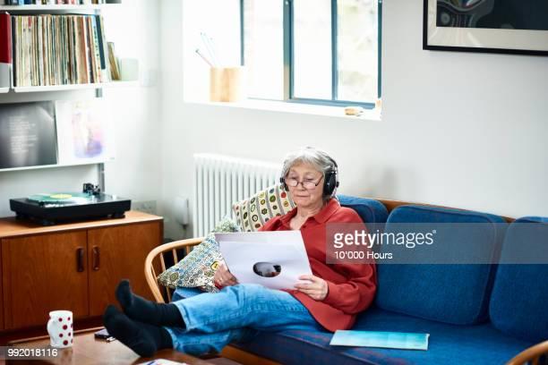 senior woman on sofa wearing headphones listening to music - 65 69 jahre stock-fotos und bilder