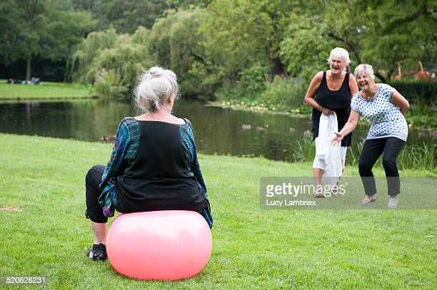 senior woman on space hopper, her friends laughing - hoppity horse stock photos and pictures