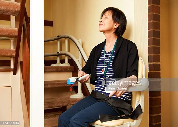 senior woman on stair lift - elevador de escada imagens e fotografias de stock