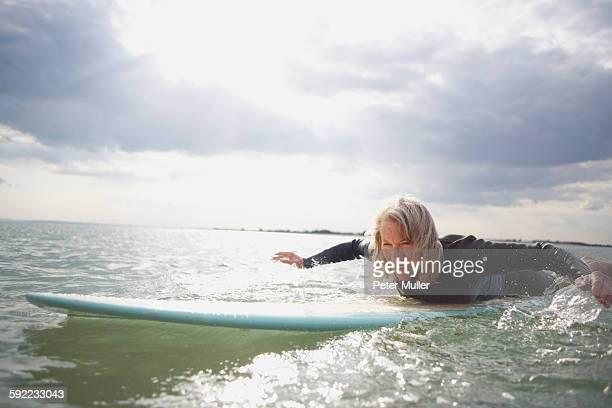 Senior woman on surfboard in sea, paddleboarding