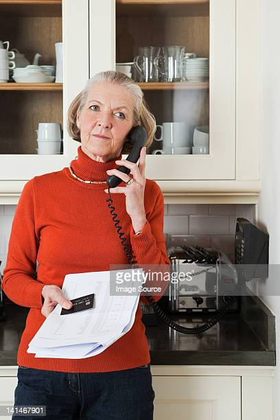 Senior woman on telephone with statement and credit card