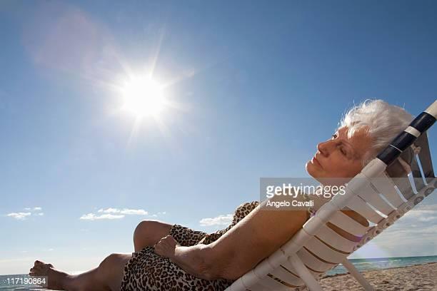 sênior mulher na praia - cadeira recostável - fotografias e filmes do acervo