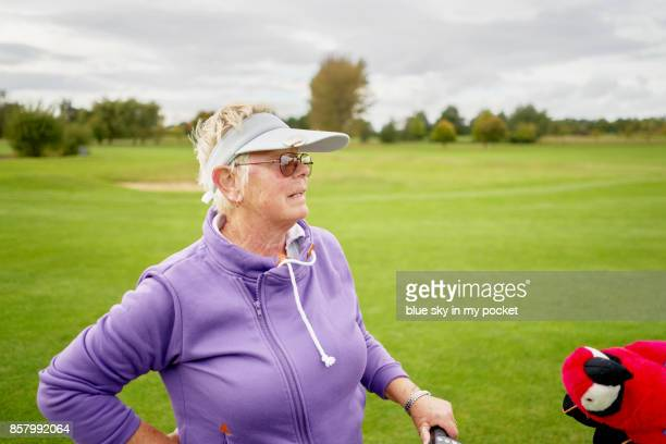 A senior woman on the golf course, with her parrot club protector.