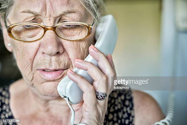 Senior woman on the phone with a look of  surprise