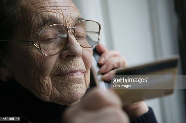 Senior woman on the phone with credit card
