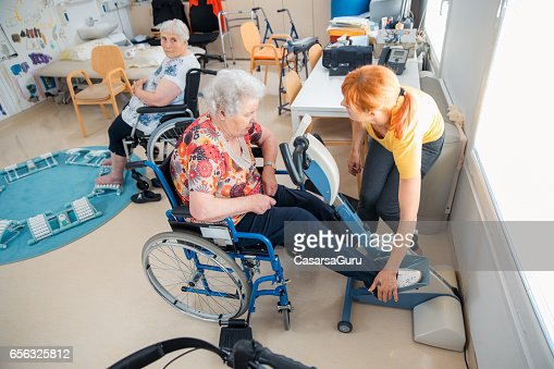 Senior Woman On Wheelchair Having Physical Therapy On Exercise