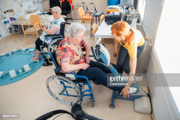 Senior Woman On Wheelchair Having Physical Therapy On Exercise Bike
