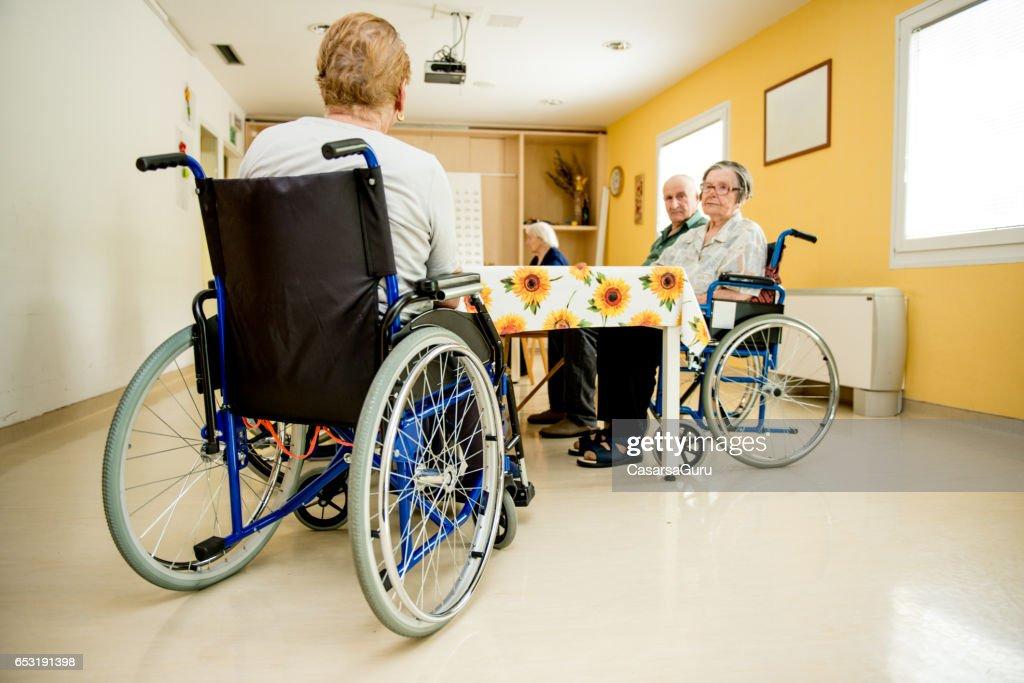 ダイニング ルームで車椅子で待ってる年配の女性 : ストックフォト