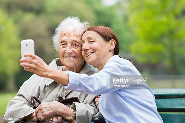 Senior woman on wheelchair with home caregiver in the park