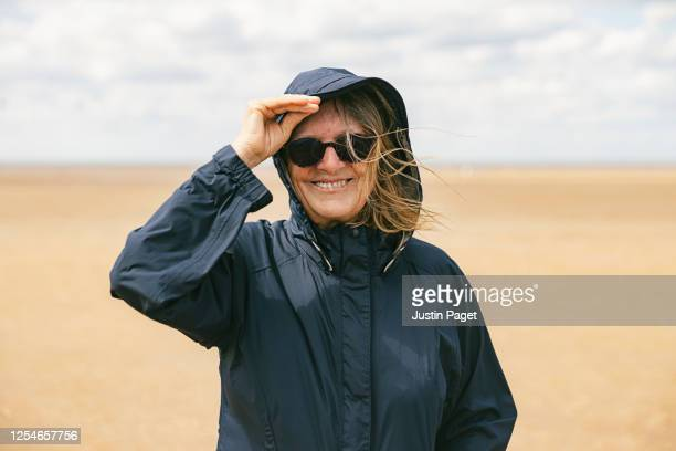 senior woman on windy beach - coastline stock pictures, royalty-free photos & images