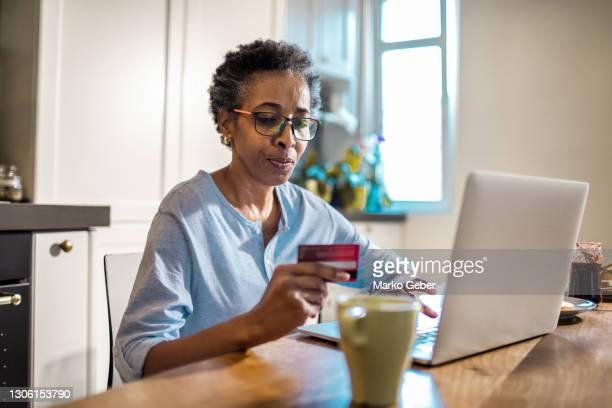 senior woman online shopping on her laptop - healthcare stock pictures, royalty-free photos & images