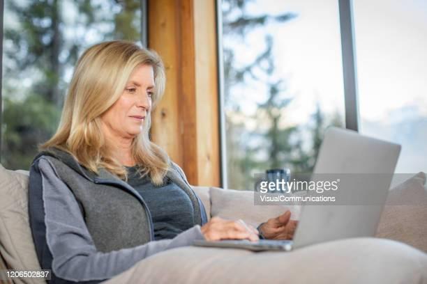 hogere vrouw online het winkelen op laptop van het comfort van huis. - alleen één seniore vrouw stockfoto's en -beelden