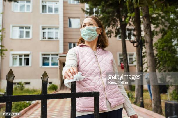 senior woman opening door handle with an antiseptic wipe - antiseptic wipe stock pictures, royalty-free photos & images