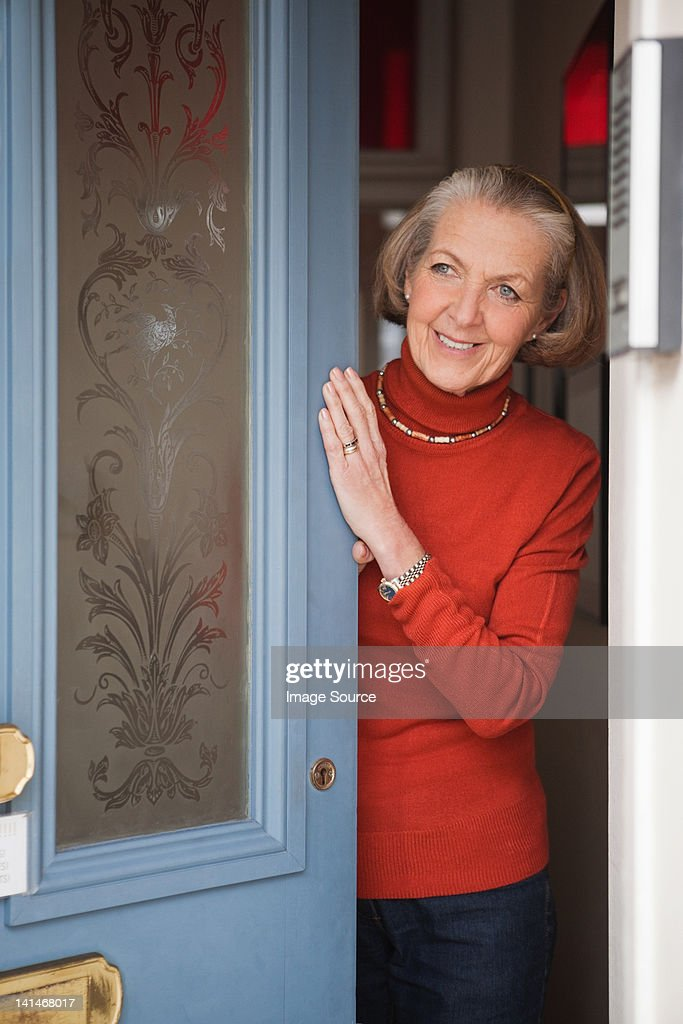 Senior woman opening front door : Stock Photo