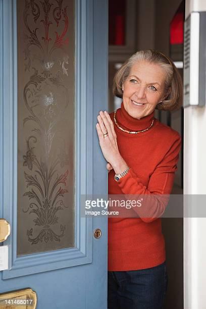 Senior woman opening front door