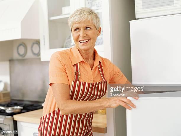 senior woman opening the door of a refrigerator