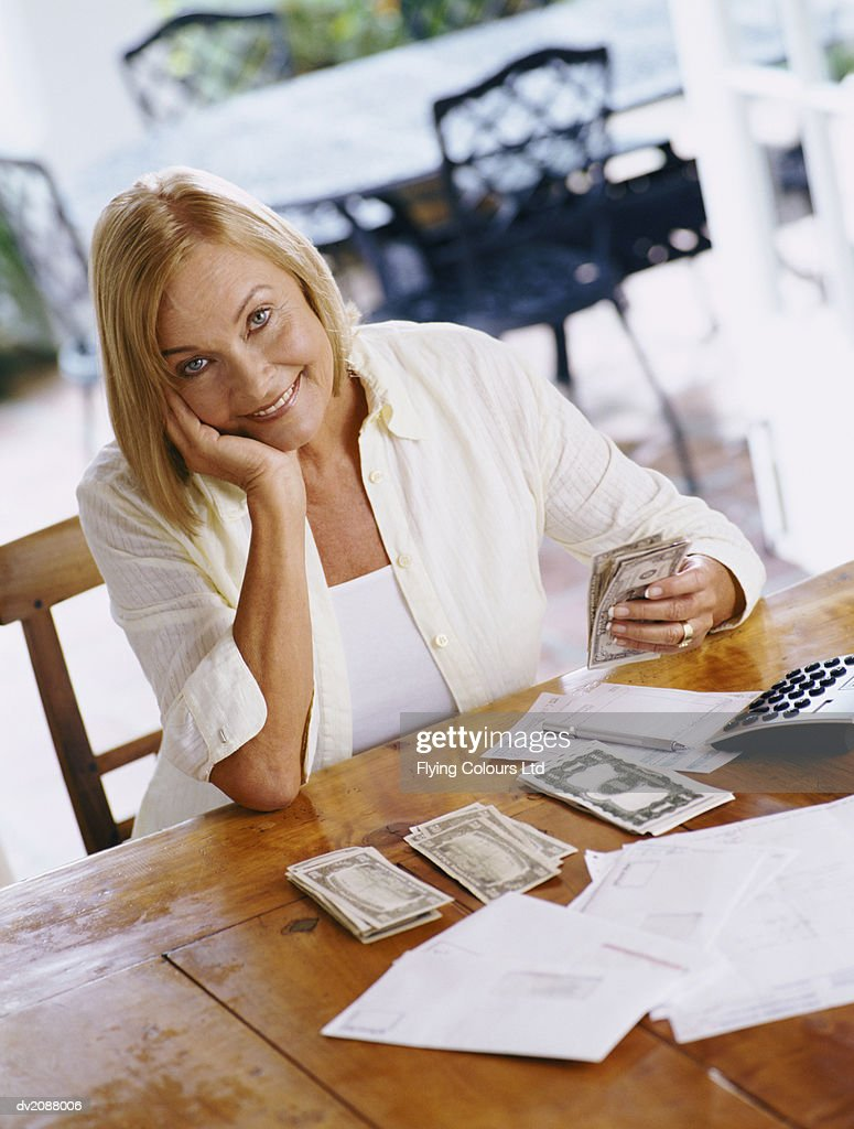 Senior Woman Organising Her Personal Finances at a Wooden Kitchen Table : Stock Photo